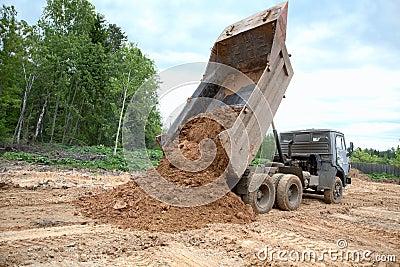 Dump-body truck unloads a ground
