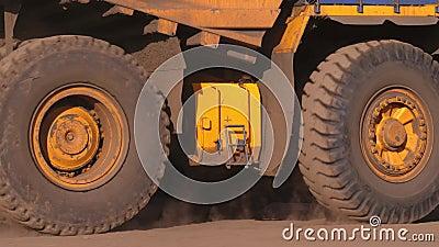 dump truck Caminhão de mineração Um caminhão gigante monta em um close-up tecnologico da estrada poeira de debaixo das rodas vídeos de arquivo
