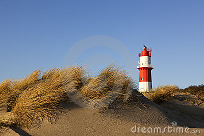 Dunes at Borkum beach and small lighthouse