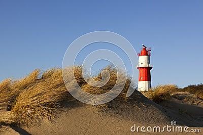 Dunes at Borkum beach and small lighthouse