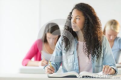 Durchdachte jugendliche die am schreibtisch sitzt for Schreibtisch jugendliche
