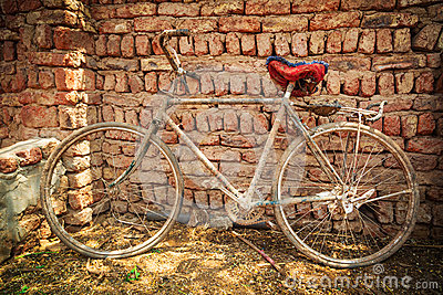 Dusty old bike at brick wall