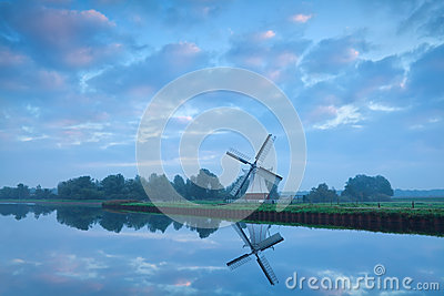 Dutch windmill close to river during calm sunrise