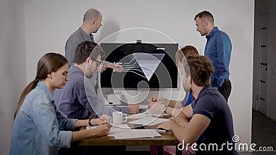 Dwóch ekspertów występuje na spotkaniu biznesowym i przedstawia plan sprzedaży w biurze zbiory