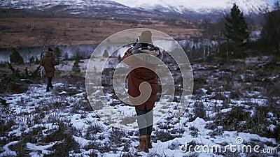 Dwóch turystów chodzących w zwolnionym tempie przez wieś w kierunku śnieżnych szczytów górskich na tle Osoba zbiory wideo