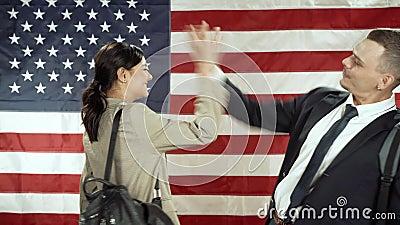 Dwóch uśmiechniętych studentów wita się na tle amerykańskiej flagi zbiory