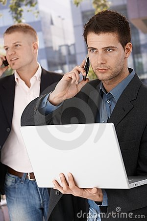 Dwa biznesmenów ruchliwie robi rozmowa telefonicza