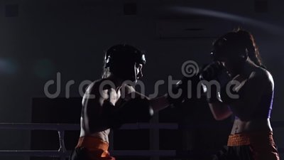 Dwa dziewczyny w hełmach boksują ich nogi w pierścionku w zmroku i ręki swobodny ruch zbiory