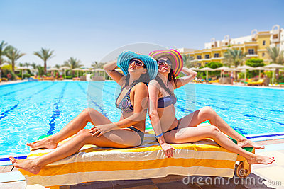 Dwa garbnikującej dziewczyny przy pływackim basenem
