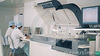 Dwa laboranckiego pracownika pisać na maszynie na klawiaturach, podczas gdy specjalny wyposażenie pracuje przy kliniką zbiory