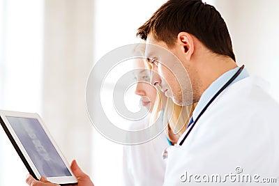 Dwa lekarki patrzeje promieniowanie rentgenowskie na pastylka komputerze osobistym