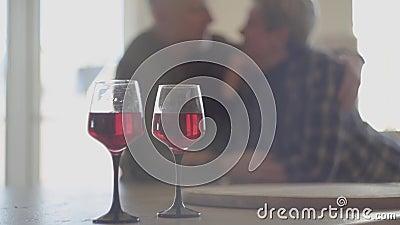 Dwa szkła czerwone wino w tle i są sylwetką starsza para Obsługuje chwyt kobiety i całuje jej nos Bela zbiory