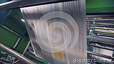 Dwa widoku cały masyw drukowani papierowi prześcieradła dostaje przetwarzający przemysłową maszyną zbiory