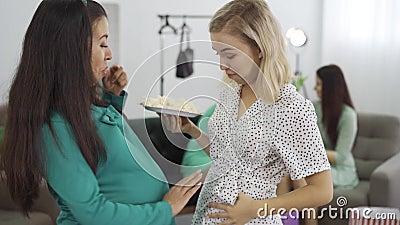 Dwie atrakcyjne kaukaskie kobiety w ciąży jedzące słodycze i pieszczące brzuchy Spodziewana kobieta i jej przyjaciółka... zdjęcie wideo