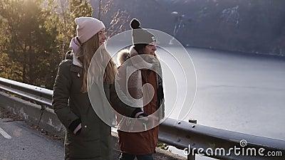 Dwie kobiety turystki w zimowych płaszczach chodzące w zwolnionym tempie po długiej drodze przez wieś w kierunku śnieżnego zdjęcie wideo