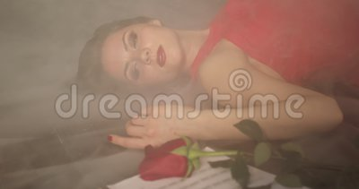 A dying brunette girl lies in a smoke on the floor. A fashionable woman in a red dress and bright makeup suffers from unhappy love. 4K footage stock video footage