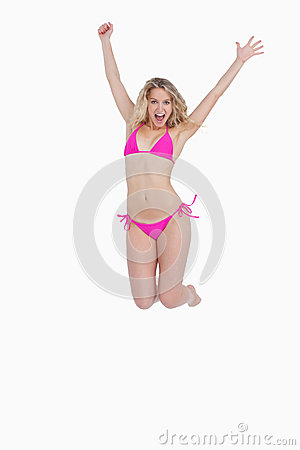 Dynamic blonde woman energetically jumping