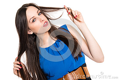 Attractive brunette in blue dress playing with her hair