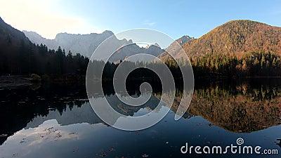 Dynamisch bewegen in het meer van Laghi di Fusine, met reflectie over de alpenbergen op kalm water stock video