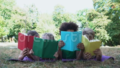 Dzieci czytające książki, leżąca mata w parku, klub miłośników książek, koncepcja edukacji zbiory wideo