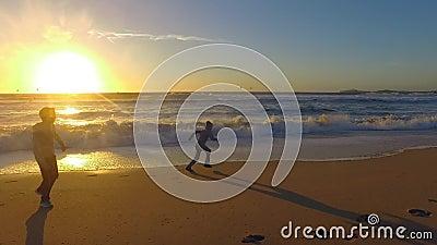 Dzieciaki bawić się przy plażą, zmierzch w Przyrodniej księżyc zatoce zbiory
