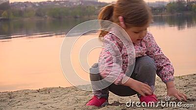 Dziecko bawiące się w piasek na plaży w pobliżu rzeki lub jeziora zdjęcie wideo
