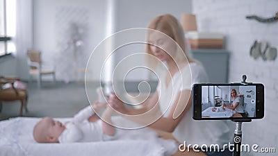 Dziecko gimnastyka, blogger matka ćwiczenia dla małej córki i rejestry żyją tutorial wideo na kamery wiszącej ozdobie zdjęcie wideo