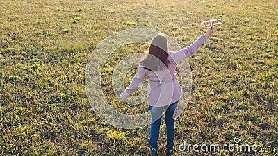Dziewczyna biegnie przez pole, trzymając samolot, symuluje lot Jesienna niedziela Rozrywka na zewnątrz zbiory