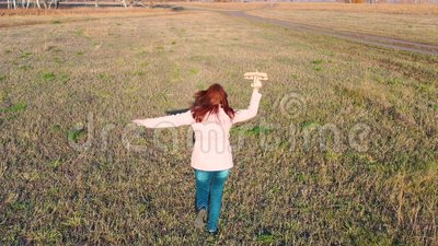 Dziewczyna biegnie przez pole, trzymając samolot, symuluje lot Jesienna niedziela Rozrywka na zewnątrz zdjęcie wideo
