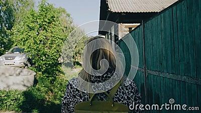 Dziewczyna chodzi za jednopiętrowymi intymnymi domami Tam są mnóstwo drzewa Kamera podąża dziewczyny od za Wolny playback zbiory