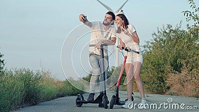 Dziewczyna i jej chłopak na elektrycznych skuterach robią selfie na tle farm wiatrowych zdjęcie wideo