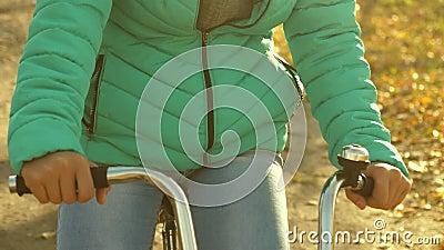 Dziewczyna utrzymuje jej ręki na kole i jedzie bicykl na drodze z zatartymi liśćmi w złotej jesieni Zakończenie zbiory wideo