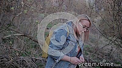 Dziewczyna w niebieskich dżinsach przechodzi pod gałąź zgina jej głowę Pi?kna filmowa rama Wolny playback zbiory wideo