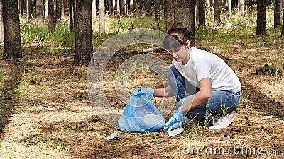 Dziewczyna wolontariuszka zajmuje się środowiskiem, zbierając śmieci w lesie Koncepcja troski o środowisko zdjęcie wideo