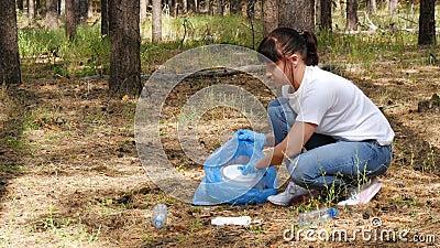 Dziewczyna wolontariuszka zbiera śmieci w torbie ulegającej biodegradacji, dbając o środowisko Koncepcja ochrony środowiska zbiory