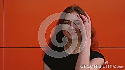 Dziewczyna z brązowymi włosami stawia na ścianie, która trzęsie włosami zbiory wideo