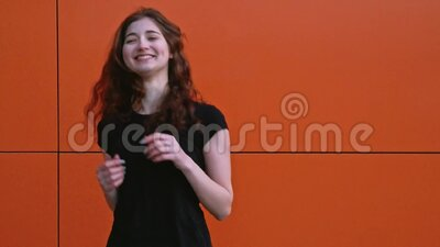 Dziewczyna z rudą tańcząca w przysięgach sportowych na czerwonej ścianie w zwolnionym tempie zbiory wideo