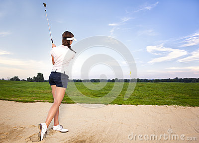 Dziewczyny golfowy gracz w bunkieru odpryskiwania piłce.