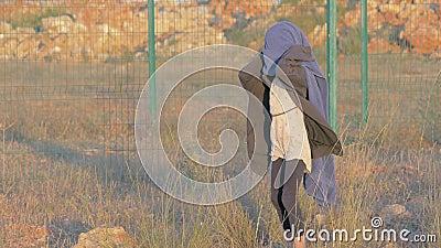 Dziwacznej małej dziewczynki chodzący obóz uchodźców zakrywający od zimna z błękitną koc Obszaru granicznego miejsce zakwaterowan zbiory