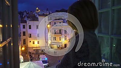 E Automobile dell'ambulanza sulla via La giovane donna emozionante guarda fuori la finestra della sua casa stock footage