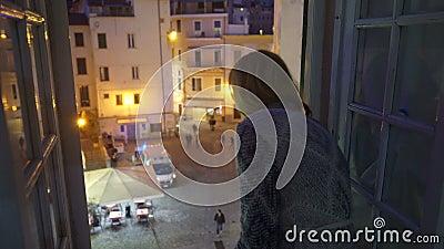 E Coche de la ambulancia en la calle La mujer joven emocionada mira hacia fuera la ventana de su casa almacen de metraje de vídeo