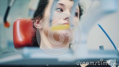 Eine junge Frau am Zahnarztberuf Während dieser Zeit sitzt er auf einem zahnroten Stuhl Während dieser Zeit sitzt er ernstlich stock video
