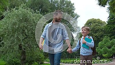 Le parent portent l'enfant à l'école Élève d'école primaire aller étudier avec le sac à dos dehors Le père et le fils vont main d banque de vidéos