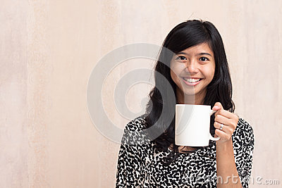 Beautiful asian girl holding a white mug and smiling to the camera