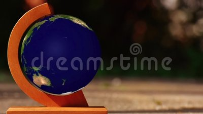 Spinning Earth globe. Earth globe spinning on orange axis on tabletop