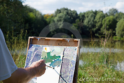 Easel artist in nature. Draw landscape from nature