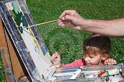 Easel artist in nature. Girl learns to paint with