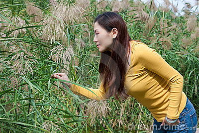 East asian woman bending over picking flowers