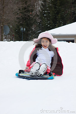 Free East Indian Girl Toboganning In The Snow Royalty Free Stock Photo - 28671955