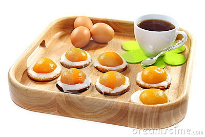 Easter biscuits and a cup of tea on wooden tray.